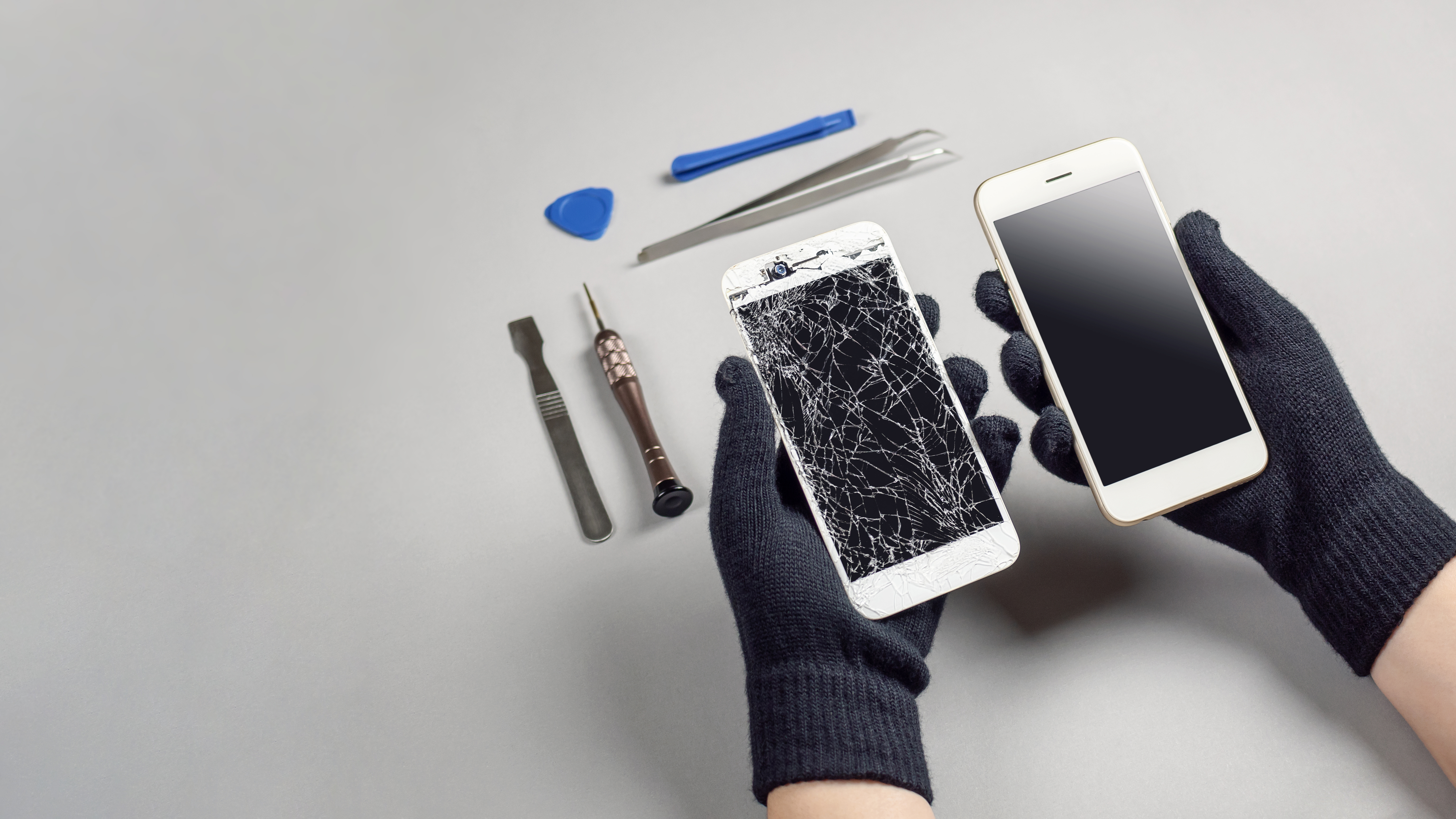 Technician preparing to repair and replace new screen broken and cracked screen smartphone repairing on desk.